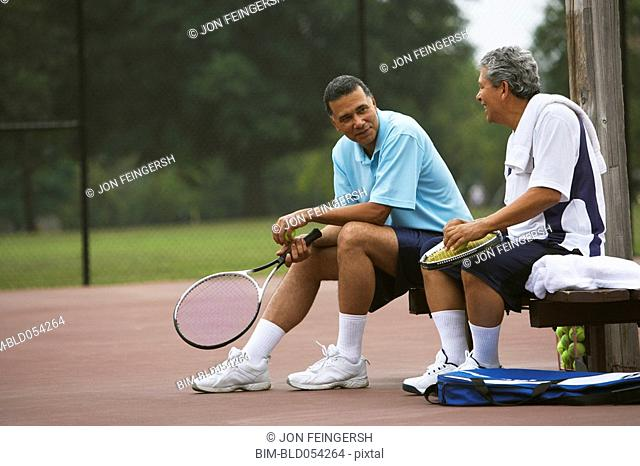 Multi-ethnic men talking on tennis court