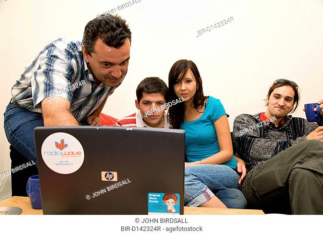 Group of friends in shared house looking at information on laptop