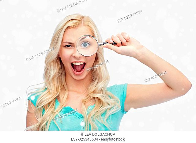 vision, exploration, investigation, education and people concept - happy smiling young woman or teenage girl looking through magnifying glass over snow