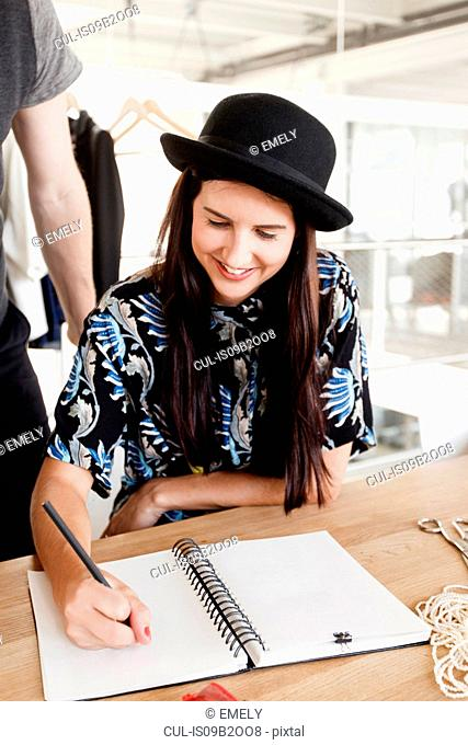 Fashion designer sketching fashion design smiling