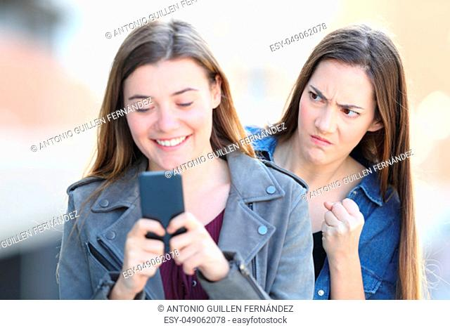 Front view portrait of an angry woman spying her friend using phone in the street
