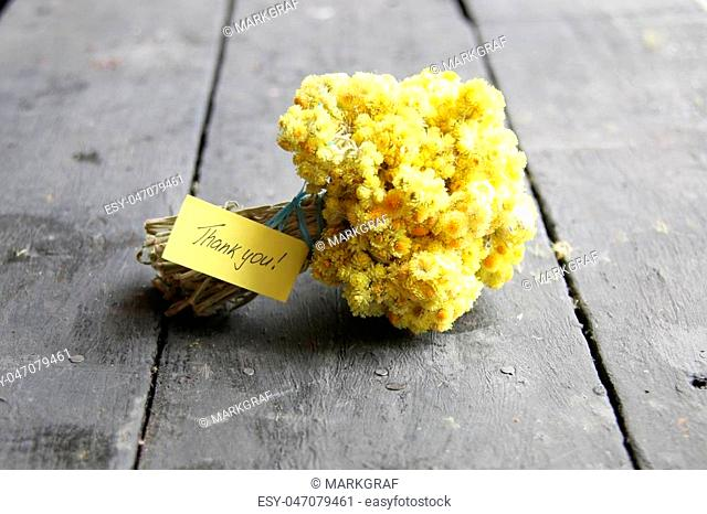Thank you lettering and yellow flowers on wooden table