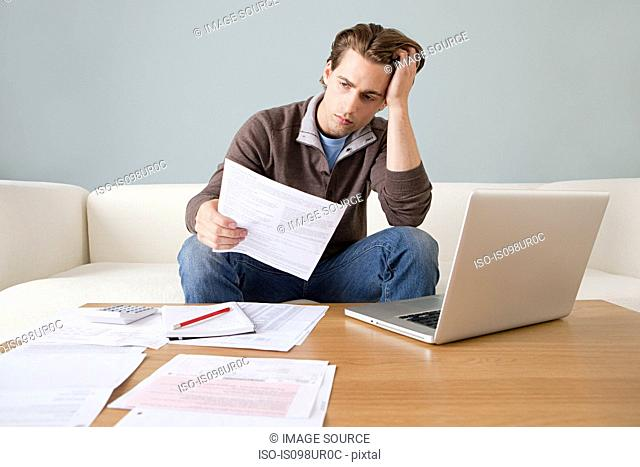 Worried young man with paperwork using laptop