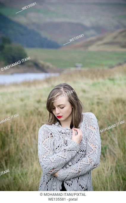 Beautiful young woman standing in the countryside looking away