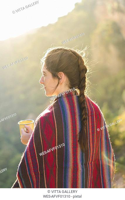Spain, Alquezar, woman with braid and coffee mug at backlight