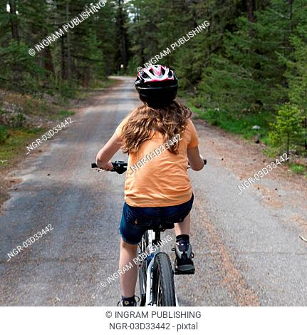 Girl riding a bicycle, Jasper National Park, Alberta, Canada