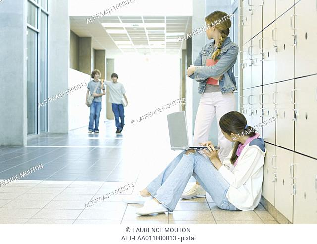 Two high school girls by lockers, watching teen boys approaching