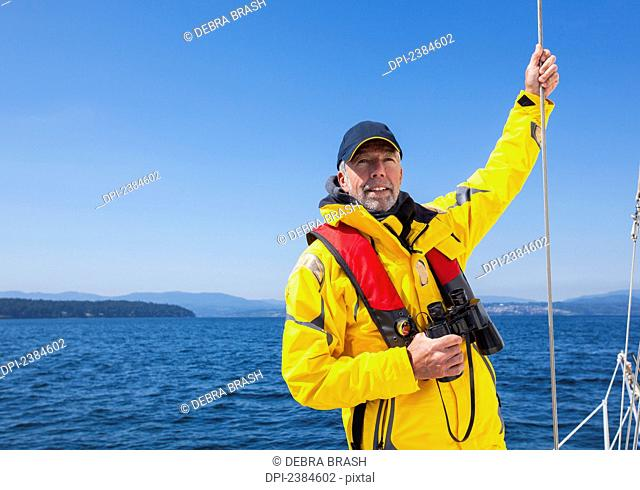 A senior man with binoculars looks over the Gulf Islands while sailing near Vancouver Island; British Columbia, Canada