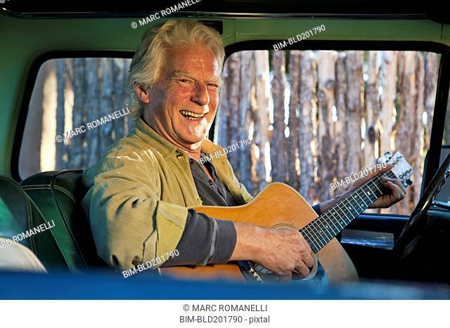 Caucasian man playing guitar in truck