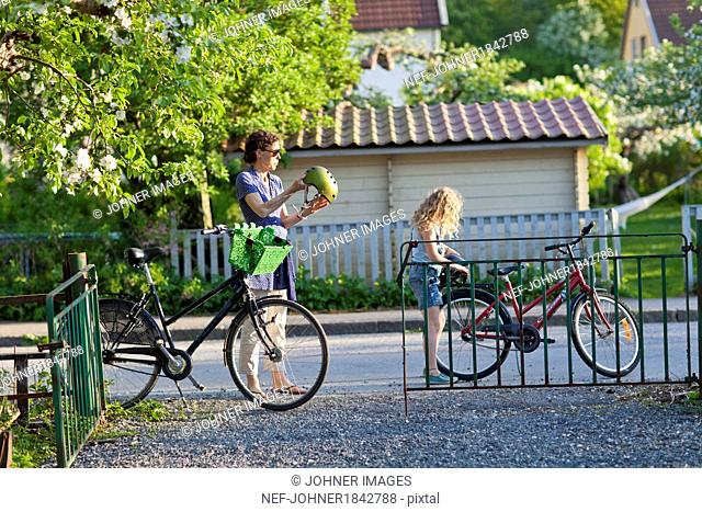 Mother and daughter preparing for bike ride