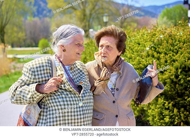 Happy old senior women telling stories each other in park