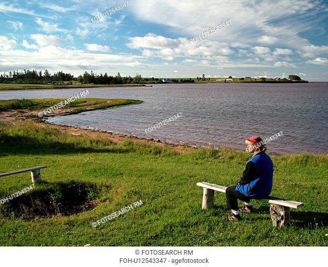 Canada, Prince Edward Island, Gulf of Saint Lawrence, Prince County, Northumberland Strait, woman sitting on bench along coast
