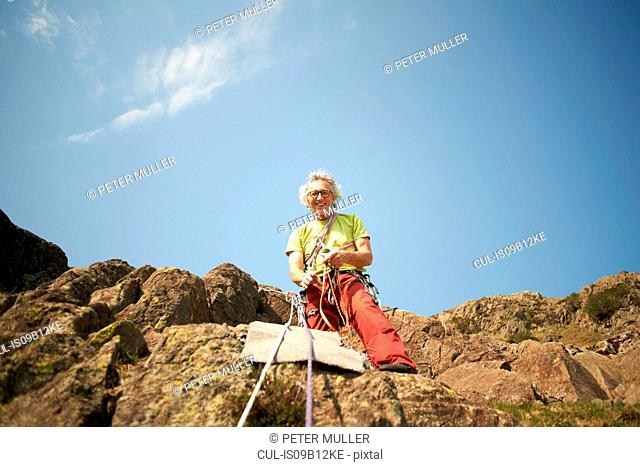 Low angle view of rock climber holding climbing rope looking at camera smiling