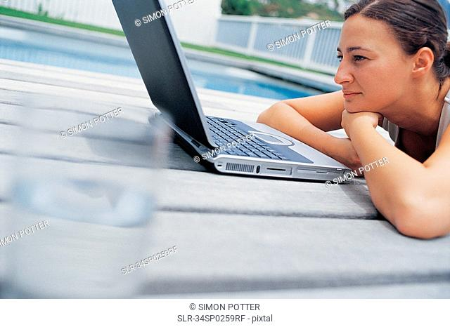 Woman using laptop by pool