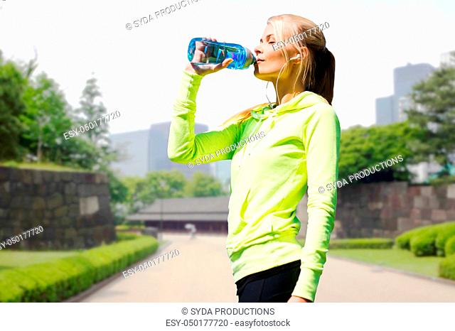 woman drinking water after exercising in city park