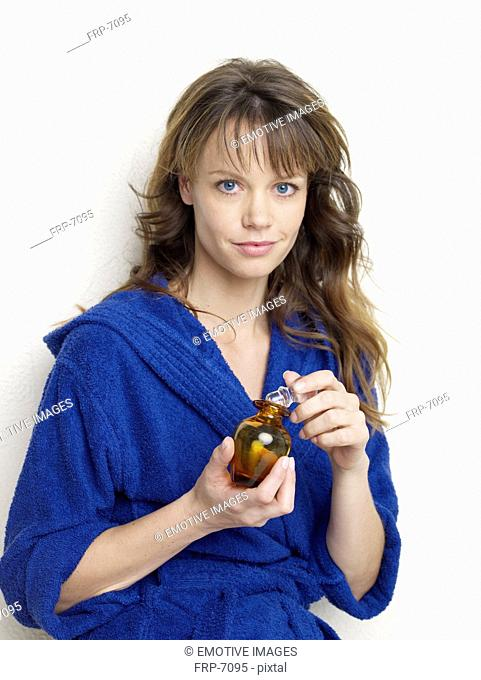 Young woman in blue bath robe holding glass bottle