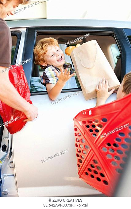 Father and sons loading groceries in car
