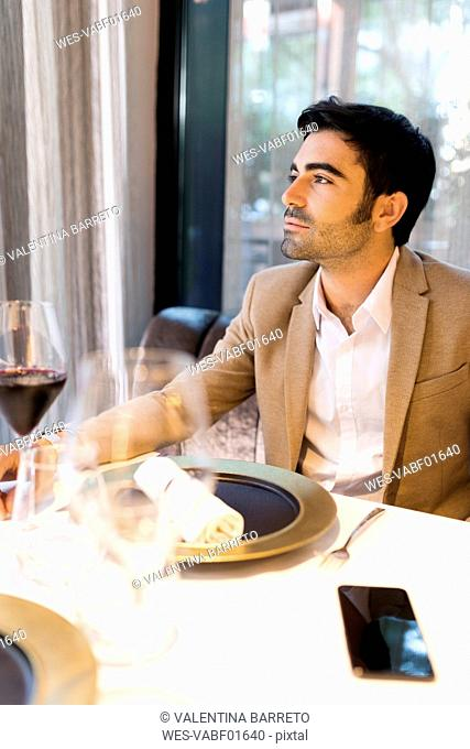 Man sitting at table in a restaurant thinking