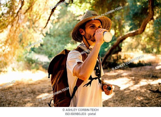 Hiker drinking from water bottle, Malibu Canyon, California, USA