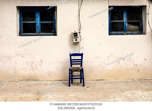A chair in front of a white wall with windows in Athens, Greece, Europe