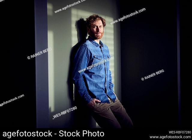 Portrait of a casual businessman leaning against a wall