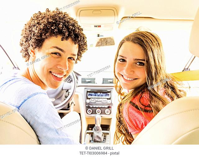 Portrait of young man and teenage girl (14-15) in car