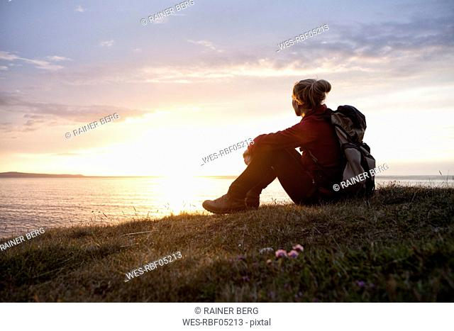 Iceland, hiker sitting on a meadow looking at view by twilight