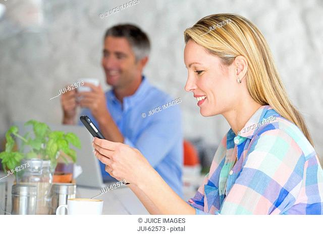 Smiling woman using cell phone at table