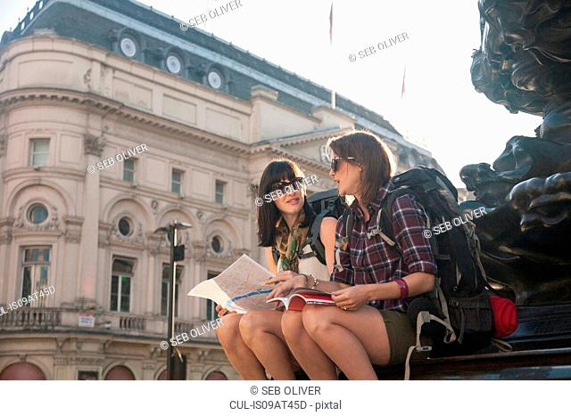 Two women backpackers sitting on statue steps with map and guide book, Piccadilly Circus, London, UK