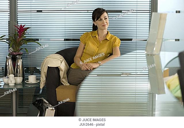 Businesswoman sitting in office reception area, waiting patiently, reception desk in foreground