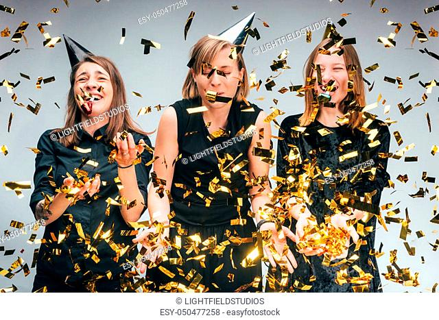 group of young beautiful women in party hats with falling confetti all around, isolated on grey