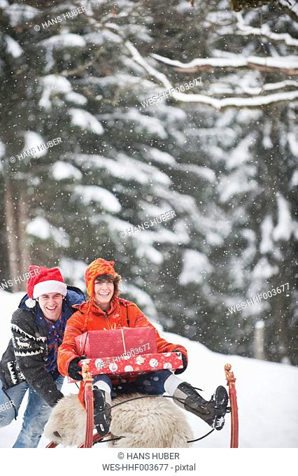 Austria, Salzburg Country, Flachau, Young woman sitting on sledge with christmas parcels and man pushing it