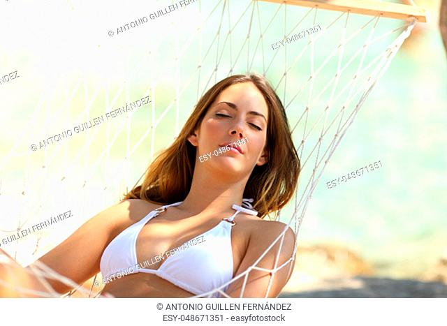 Relaxed woman wearing bikini resting on a hammock on the beach on summer vacation
