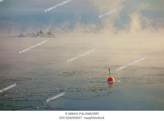 Bright red buoy floating alone in the freezing Baltic Sea in Helsinki, Finland just hours before complete freeze over of the sea on an extremely cold January...