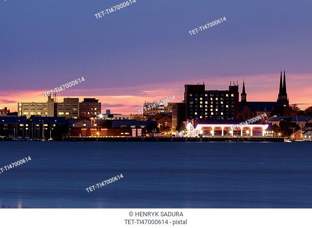 Illuminated waterfront skyline against moody sky