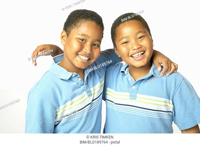 Young African twin brothers hugging and smiling