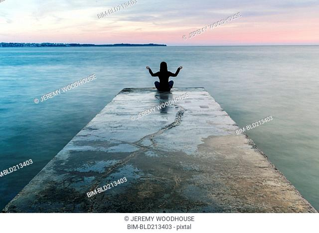 Asian woman meditating on concrete pier