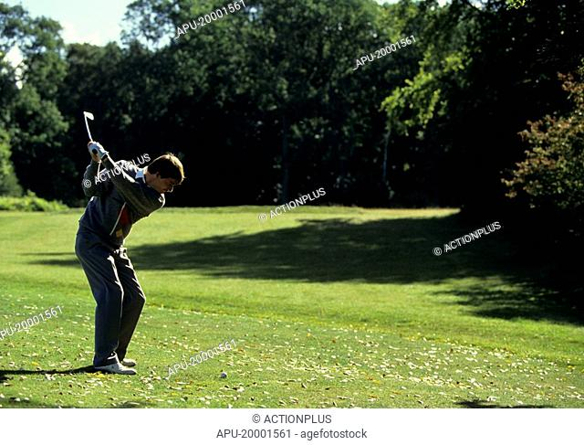 Golfer tees off on a golf course