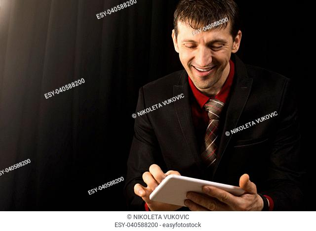 The smiling businessman is using white digital tablet on black background
