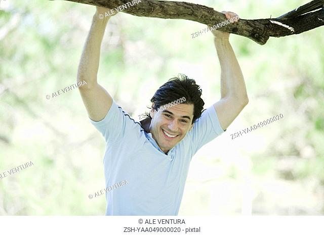 Man holding on to branch, smiling at camera