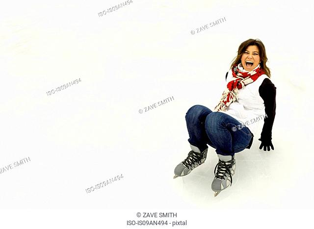 Young woman wearing ice skates, falling down laughing