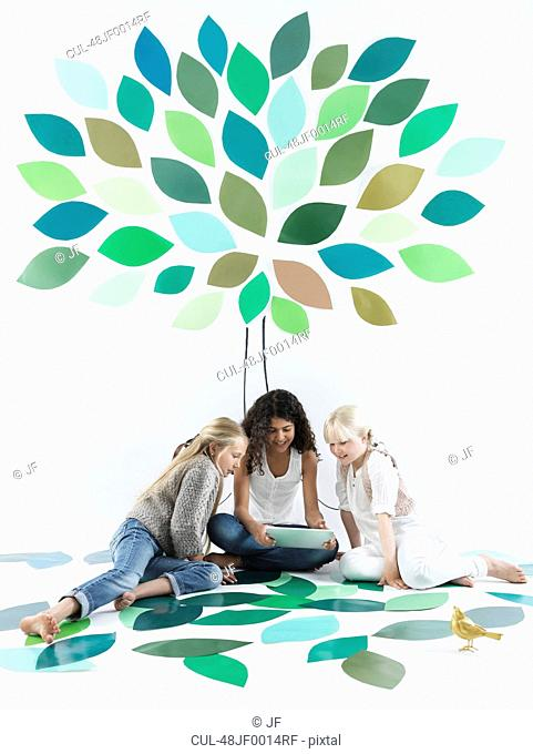 Girls talking under tree on wall