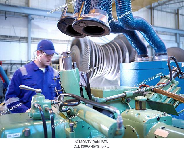 Engineer operating machinery in steam turbine repair workshop