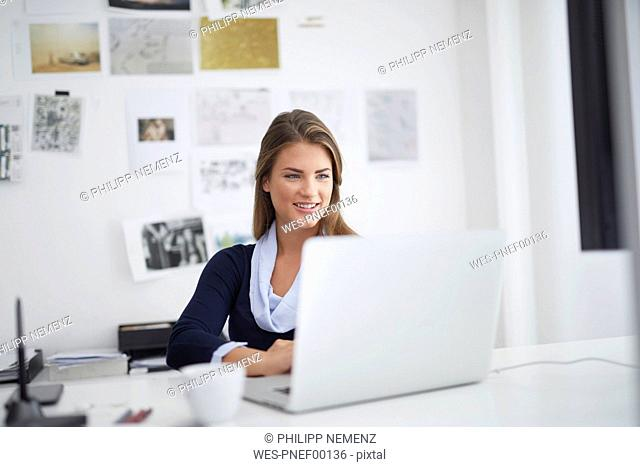Smiling young woman using laptop at desk in office
