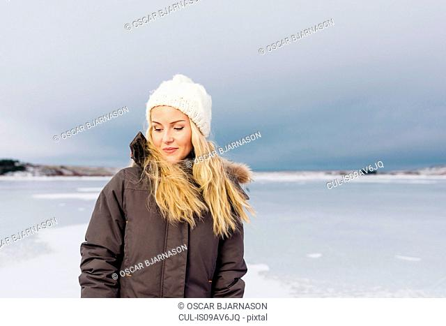 Mid adult woman by frozen lake looking down smiling