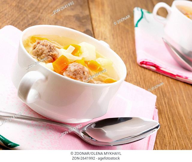 Homemade soup with meatballs on the wooden table