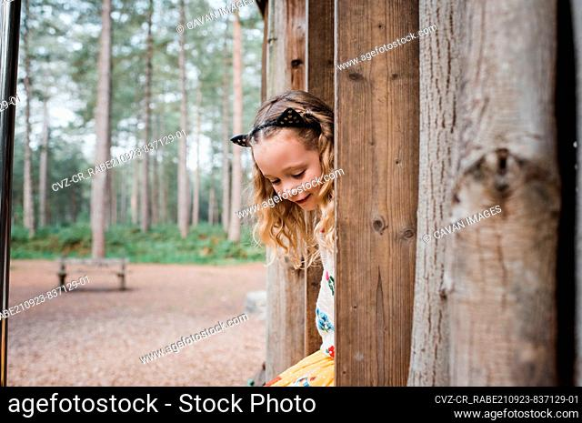 portrait of a girl climbing a tree house in the forest