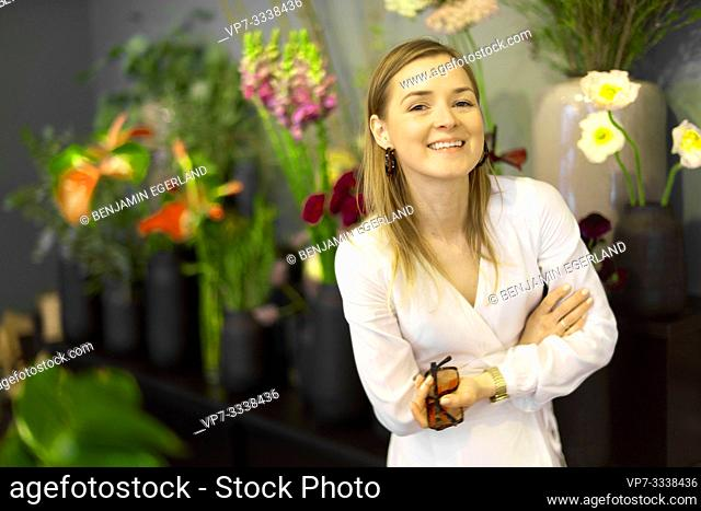 woman next to flowers