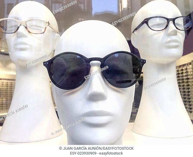 Three mannequin heads in shop window with urban reflections