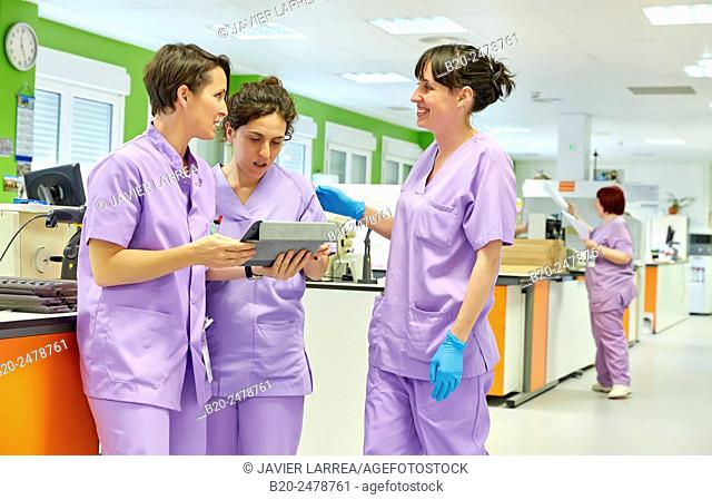 Healthcare worker with digital tablet discussing with two colleagues, Anatomic Pathology, Hospital Donostia, San Sebastian, Basque Country, Spain